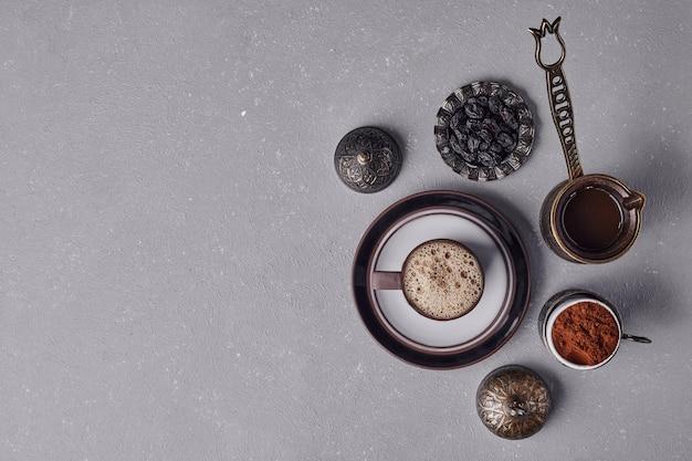 Een kopje koffie met een metalen pot en kaneelpoeder eromheen.