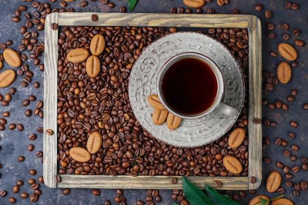 Een kopje koffie met gebrande koffiebonen en koffieboon vormige koekjes op donkere ondergrond
