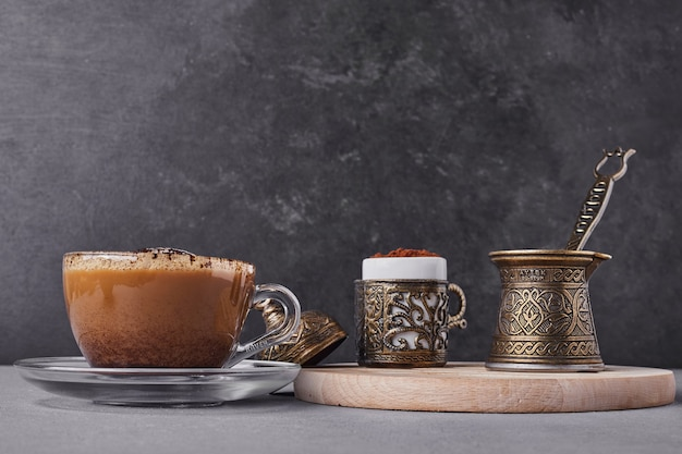 Een kopje koffie met kaneelpoeder eromheen.