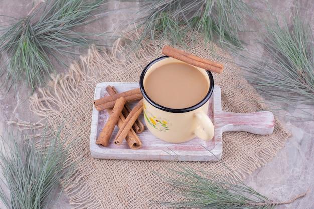 Een kopje koffie met kaneelsmaak op een houten bord