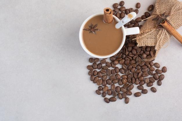Een kopje koffie met kaneelstokjes en koffiebonen op marmeren achtergrond. hoge kwaliteit foto