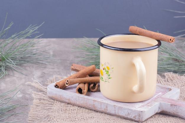 Een kopje koffie met kaneelstokjes op rustieke houten bord.
