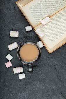 Een kopje koffie met marshmallows en boek.