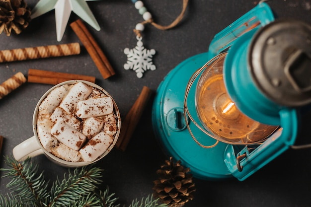 Een kopje koffie met marshmallows, kerstdecor en een kerosinelamp op donkergrijs