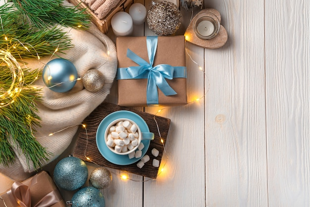 Een kopje koffie met marshmallows kerstversiering en een cadeautje