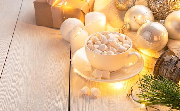 Een kopje koffie met marshmallows op een kerstachtergrond met brandende kerstverlichting