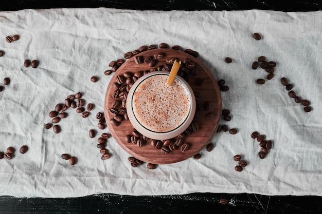 Een kopje koffie met melk op een houten bord