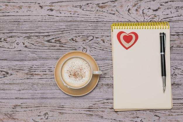 Een kopje koffie met room en kaneel, een notitieboekje en een vulpen op een houten tafel