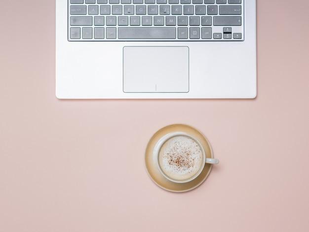 Een kopje koffie met room en kaneel en een laptop op een lichte ondergrond