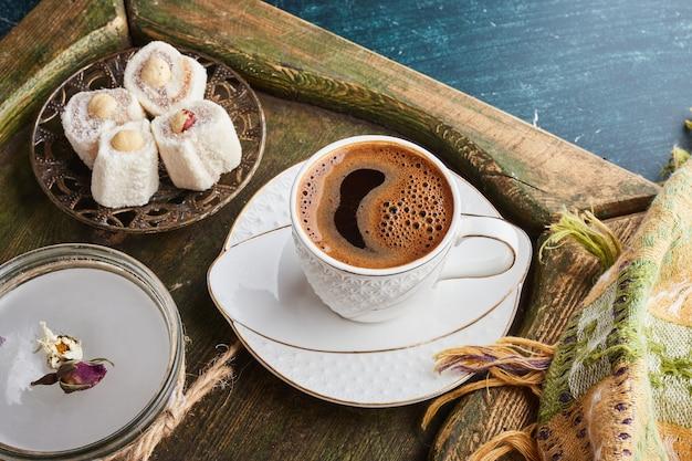 Een kopje koffie met schuim in een witte schotel geserveerd met lokum.