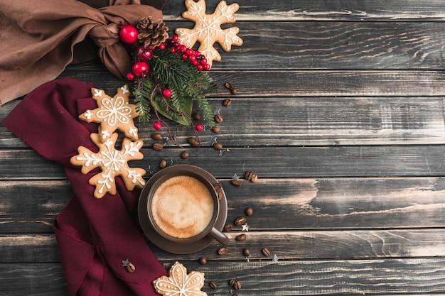 Een kopje koffie met schuim op een donker hout met peperkoek in de vorm van sneeuwvlokken.