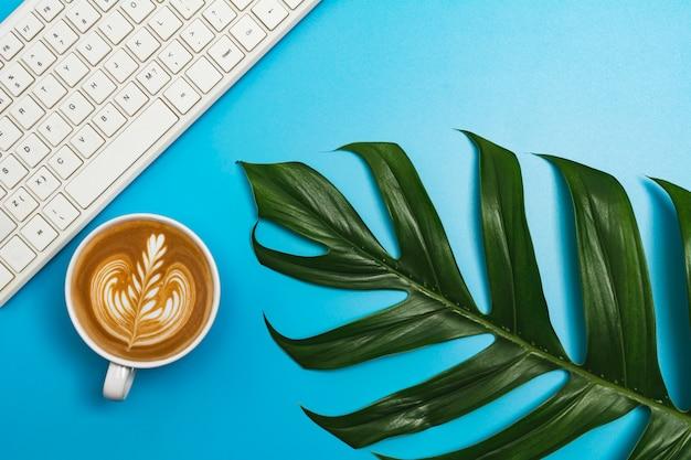 Een kopje koffie met toetsenbord en kopie ruimte op blauwe tafel. bureau en drankje concept.