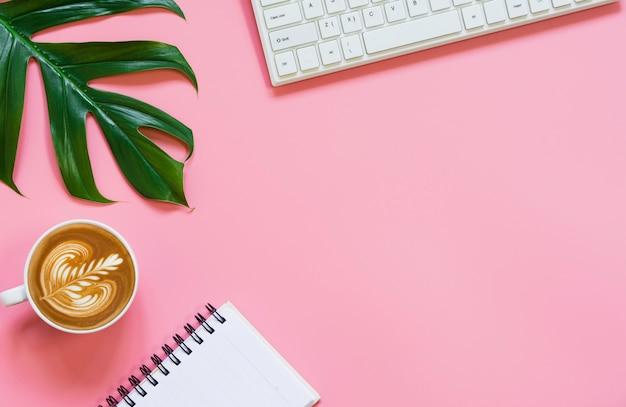 Een kopje koffie met toetsenbord en kopie ruimte op roze achtergrond. bureau en drankje concept.