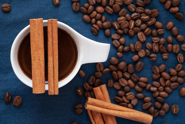 Een kopje koffie met twee kaneelstokjes erop en gebrande koffiebonen rond op een blauwe ondergrond.
