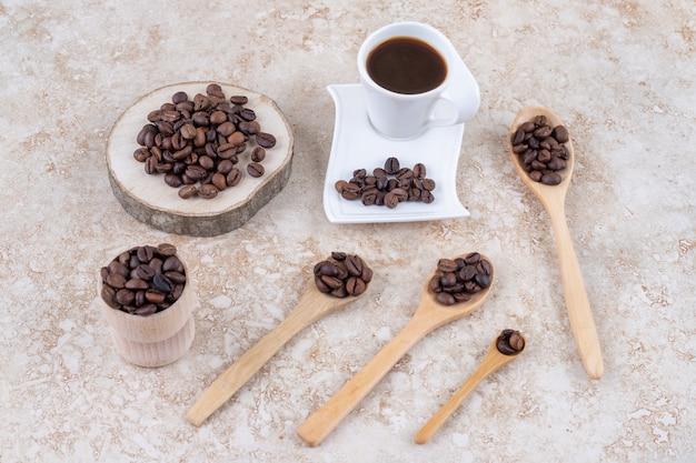 Een kopje koffie naast verschillende kleine bundels koffiebonen