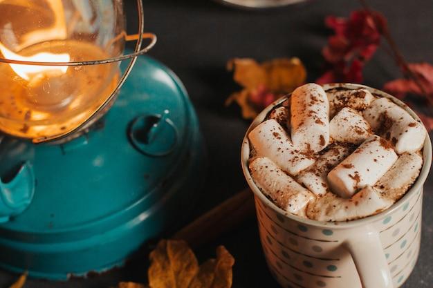 Een kopje koffie of cacao en droge herfstbladeren in het licht van een kerosinelamp op donker