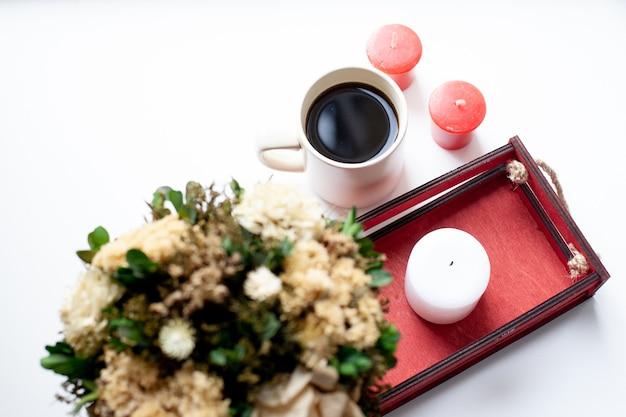 Een kopje koffie of thee, droge bloemen en witte, rode kaarsen, een rode houten kist op een beige deken.