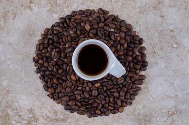 Een kopje koffie omringd met koffiebonen