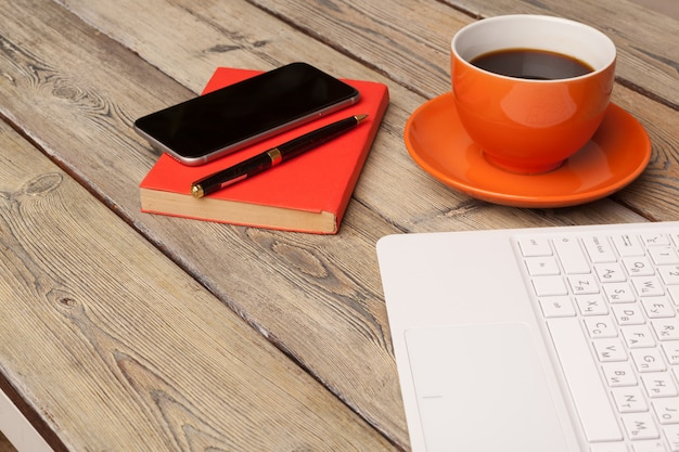 Een kopje koffie op de oranje plaat op de houten tafel. kantoor interieur
