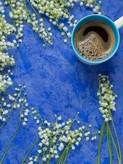 Een kopje koffie op een blauwe achtergrond en een boeket van lily of the valley. kopieer de ruimte lente ontbijt