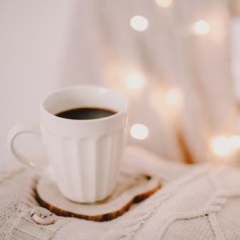 Een kopje koffie op een gebreide beige plaid met bokehlichten