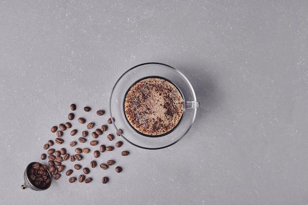 Een kopje koffie op een grijze achtergrond.