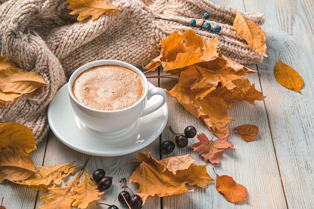 Een kopje koffie op een herfstochtend tegen de achtergrond van gebladerte en een trui