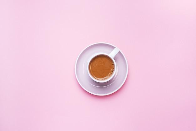 Een kopje koffie op een roze achtergrond met kopie ruimte. bovenaanzicht minimalisme.