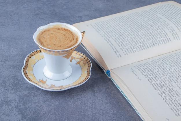 Een kopje koffie op een schotel naast het boek, op de blauwe achtergrond. hoge kwaliteit foto