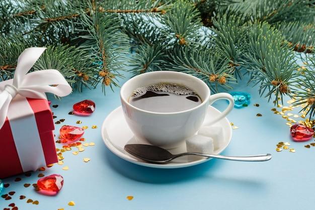 Een kopje koffie op een schotel tussen kerstversieringen, dennentakken en geschenkdozen.