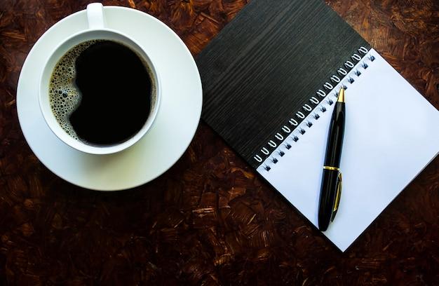 Een kopje koffie op een schoteltje naast een notitieboekje met een pen werk begint bij het ontbijt