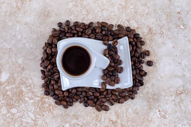 Een kopje koffie op een schoteltje zittend op een stapel koffiebonen