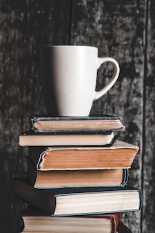 Een kopje koffie op een stapel boeken op een grijze achtergrond. onderwijs, studie, hobby's, lezen