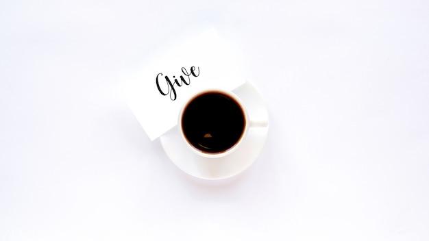 Een kopje koffie op een witte schotel met een notitie met bericht geven