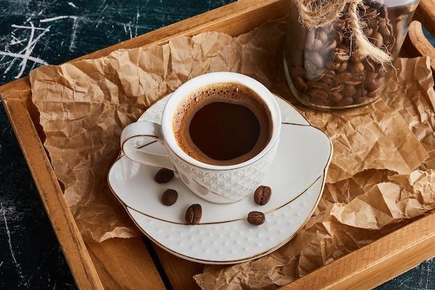 Een kopje koffie op een witte schotel.