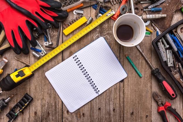 Een kopje koffie op het bureaublad met stoffig gereedschap.