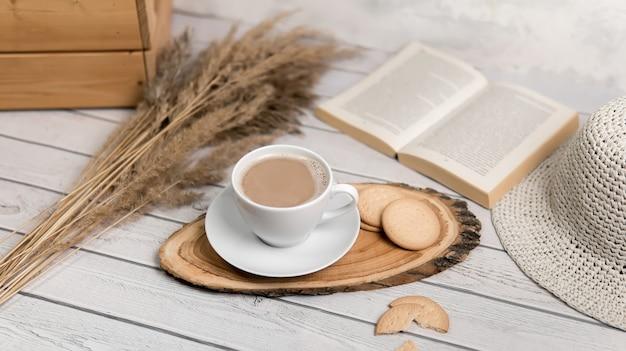 Een kopje koffie op houten schijfje met koekjes en boek. plat leggen.