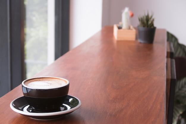 Een kopje koffie op lange houten tafel