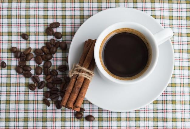 Een kopje koffie op lichte achtergrond met kaneel en koffiebonen. bovenaanzicht