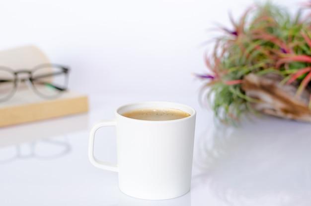 Een kopje koffie op tafel met luchtplant tillandsia, bril en boek op witte achtergrond.