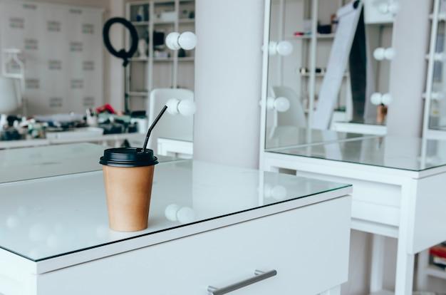 Een kopje koffie op toilettafel in de buurt van spiegel in make-up kamer
