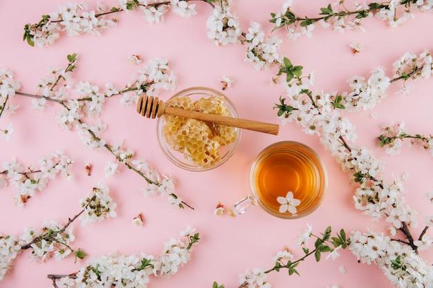 Een kopje kruidenthee en een pot honing op een roze achtergrond