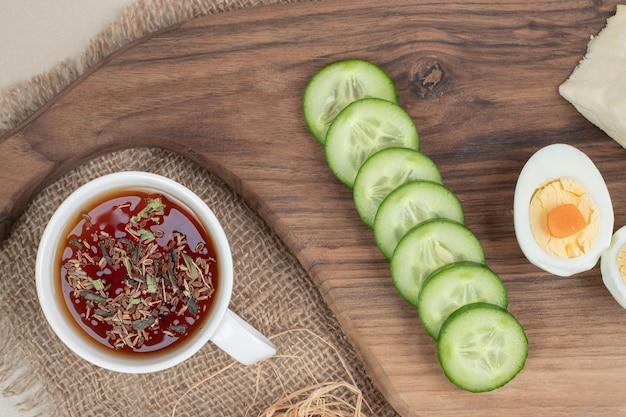 Een kopje kruidenthee met gesneden komkommer en gekookt ei.