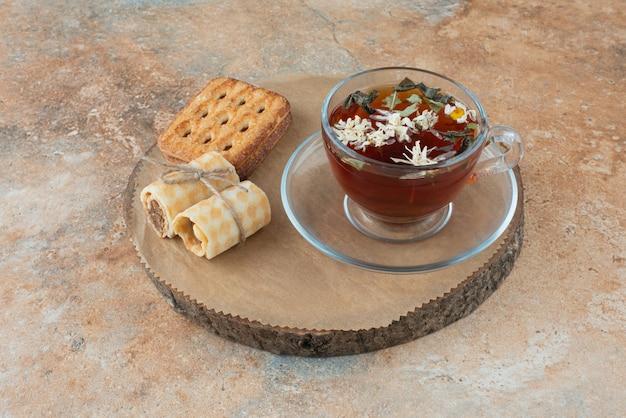 Een kopje kruidenthee met wafels op een houten bord