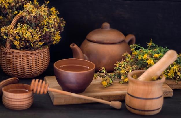 Een kopje kruidenthee op een plank op een houten tafel gemaakt van sint-janskruidgras