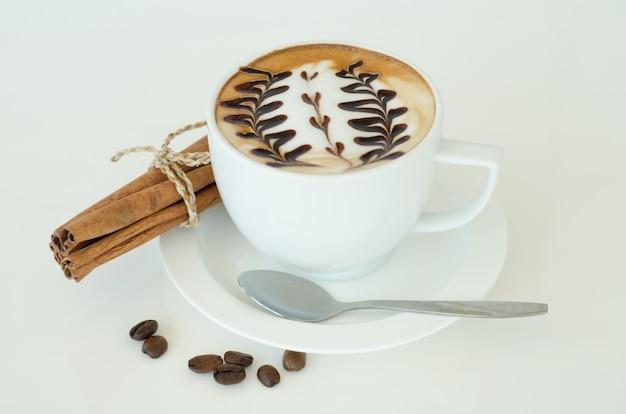 Een kopje latte kunst op witte achtergrond