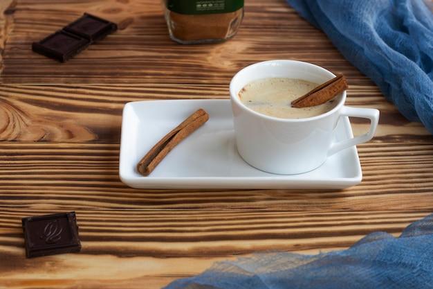 Een kopje latte met schuim staat op een vierkante schotel op een houten tafel kaneelstokjes donkere chocolade en koffiestukjes
