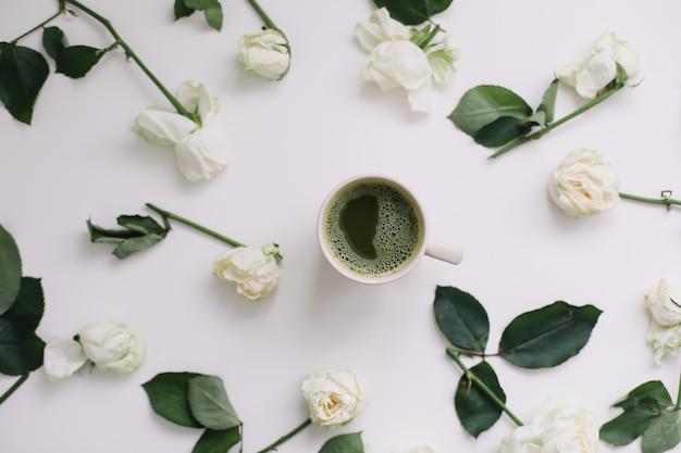 Een kopje matcha thee en rozen op witte achtergrond flatlay bovenaanzicht top
