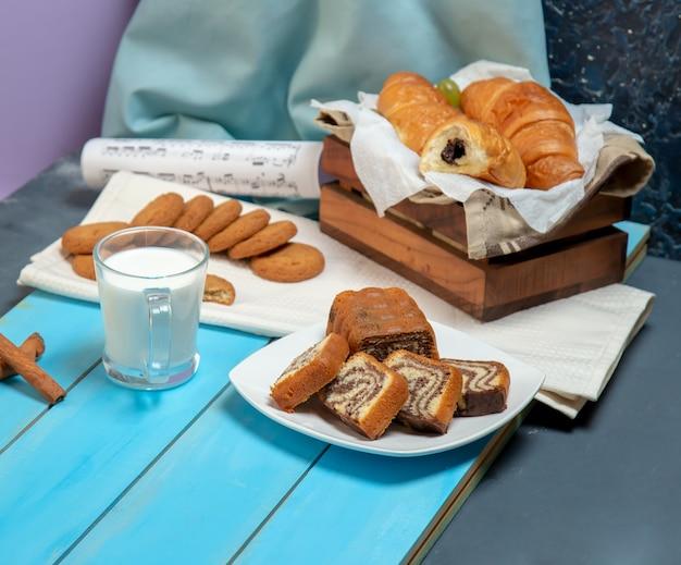 Een kopje melk met croissants en andere broodjes op tafel.