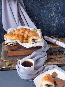 Een kopje melkachtige cappuccino met een koekje op de blauwe tafel.